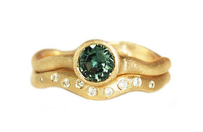 alternative engagement ring with green sapphires and diamond wedding band