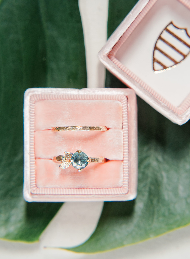 Alternative engagement ring with seafoam sapphire and gold leaves, and a unique dainty textured wedding band